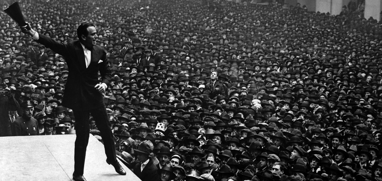 A black and white image of an excited man speaking to an enormous crowd