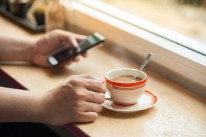 Male hand holding a cup of coffee on wood bar with another hand using smartphone in blurry background with morning scene
