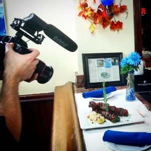 A man filming a steak and couscous dish in a restaurant