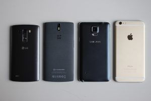 Four different popular brands of smartphone, lined up