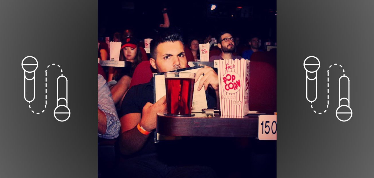 Brett Cohen sitting in a movie theater with a big tub of popcorn and a large beer. Microphones dot the sides of the picture.