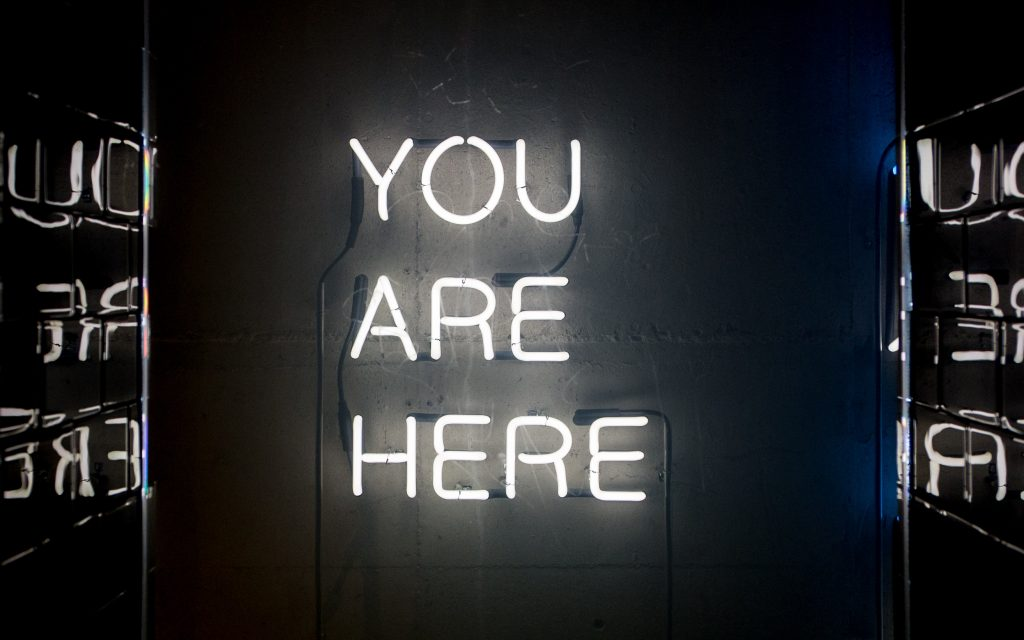'YOU ARE HERE' in neon lights - representing 'near me' searches.