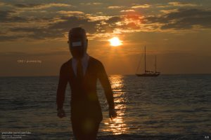 "A welding masked figure in a tie and wetsuit is seen emerging from the ocean during sunrise. There's a boat in the far distance. The caption reads, ""CBC 