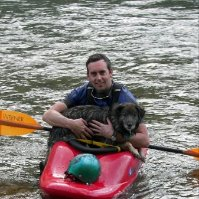 A photo of Damon Peters, in a canoe, rescuing a dog trapped in a river with many rapids.