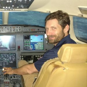 Jonathan Poston, SEO and marketer, sitting in the cockpit of a plane, showing off that he's about to do a barrel roll.