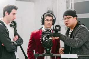 Michael Sorace, behind a camera, reviewing footage with Edward Sturm and David Labuguen. During the filming of the Millennial High Art CBC video.