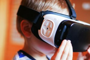 A boy playing with a virtual reality headset.