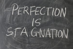"""Perfection is stagnation"" written on a chalkboard."